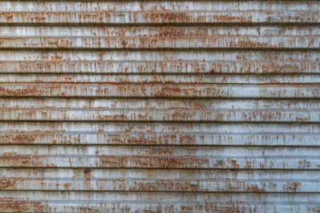 Rusty metal background with old layers of silver paint. Texture rusted shipping container. Zdjęcie Seryjne