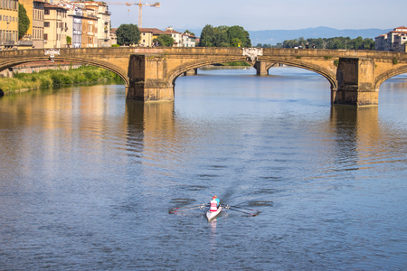 Two persons rowing boat on Arno River, Florence, Italy.