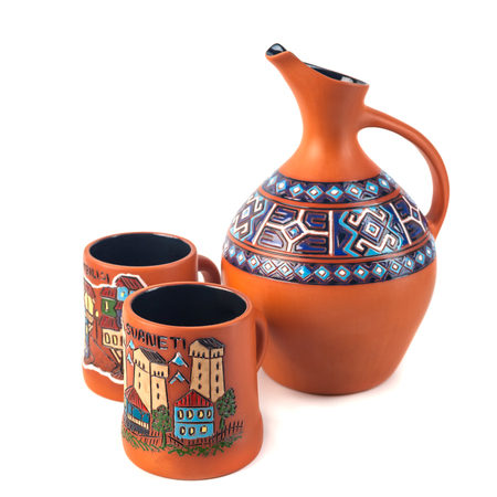 Georgian handmade ceramic (clay) jug with traditional ornaments on it, named Doqi, and cup, named tasi, for wine and water on white background.