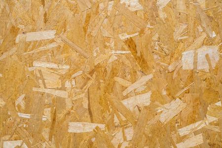 close up pressed wooden panel background, seamless texture of oriented strand board - OSB wood. Stock Photo