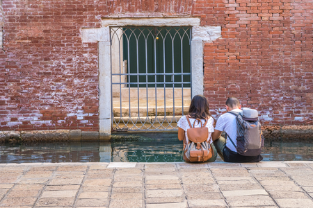 couple of tourists are sitting by the canal in Venice, Italy. Banque d'images - 119817564