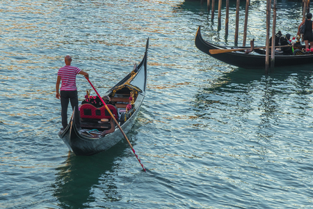 Tourists in gondolas on canal of Venice, Italy.