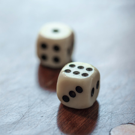 White dice on wooden background. Concept of luck, chance and leisure fun, numbers 1 and 6.