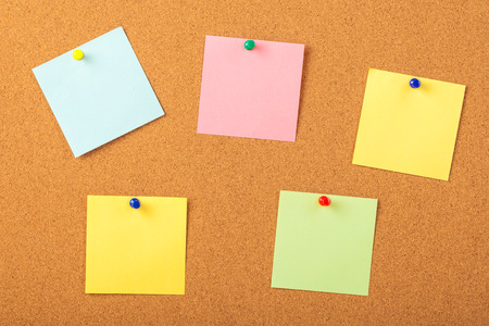 colorful papers pined with tacks on brown cork board background.