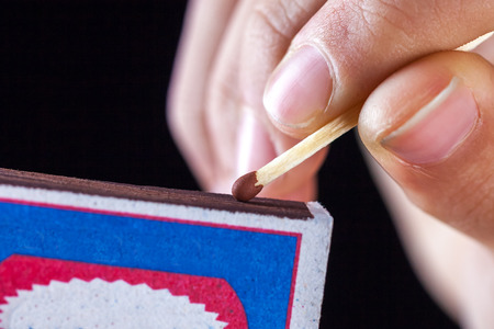 hold a matchbox while striking a match. Imagens