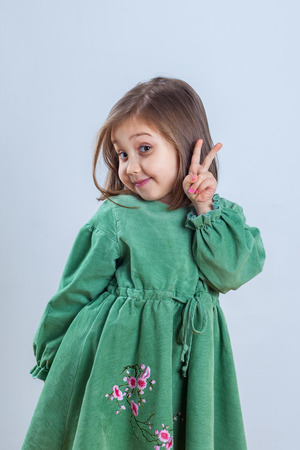 little girl in green dress posing for the camera in the studio. 写真素材