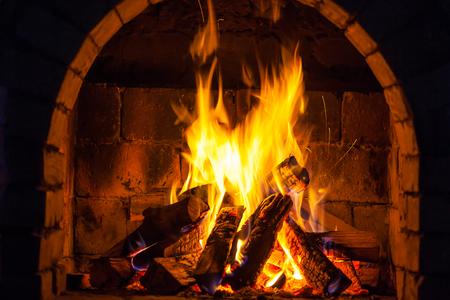 Brucia la legna in un accogliente caminetto a casa, tieniti al caldo. Archivio Fotografico