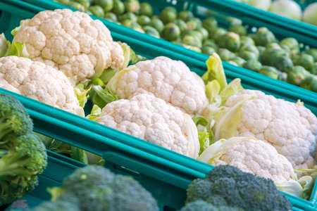 fresh cauliflower with white heads and green leaves at weekly market.