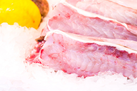 Fresh chilled out fillets of white fish on the counter of ice. fresh food.