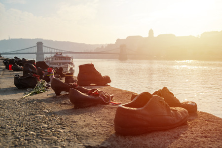 Shoes on the Danube bank - Monument as a memorial of the victims of the Holocaust during world war II on the bank of the Danube at sunset in Budapest, Hungary.