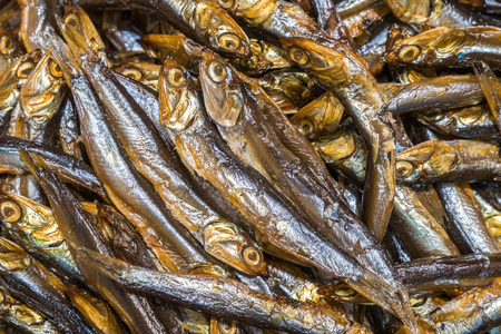Cold smoked capelin fish background, smoked fish texture.