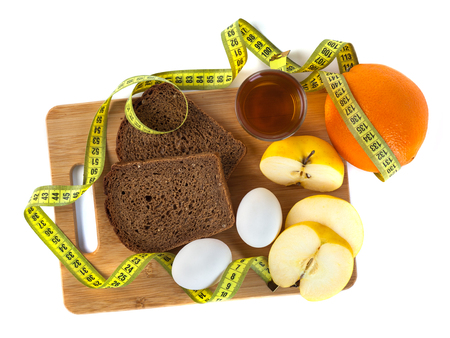 Breakfast including bread, eggs, orange, apple juice on the wooden board with measurement isolated on white. Concept of dieting and body care