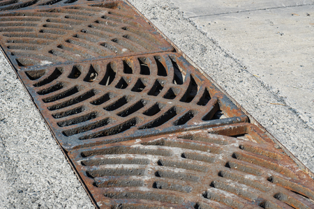 Drain of metal grate around with rough beton road surface 免版税图像