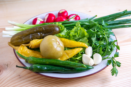 radish, parsley, onion, pickled cucumber and other vegetables on a plate, healthy food