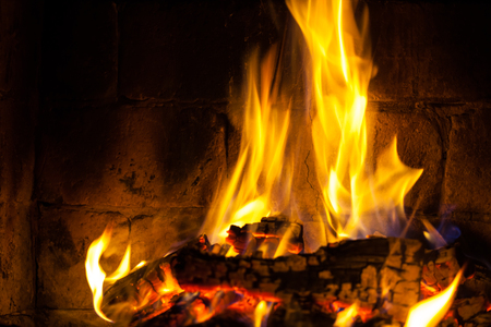 Wood burning in a cozy fireplace at home