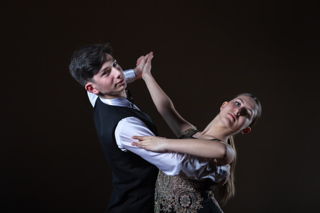 Beautiful young dancers in ballroom isolated on black background, couple dance 写真素材