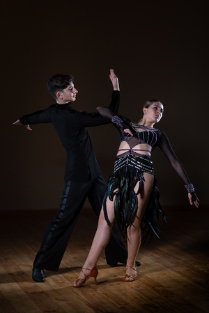 Beautiful young dancers in ballroom isolated on black background, couple dance Stockfoto