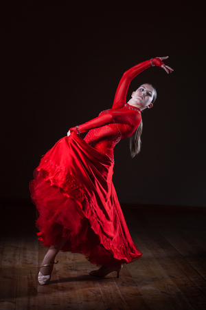 Beautiful young hispanic flamenco dancer in red dress isolated on black background