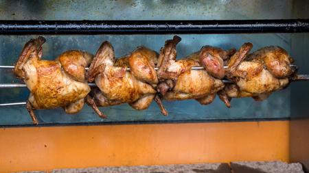 Succulent roasting chickens on a rotisserie at a market, food