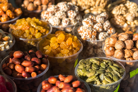 A variety of nuts in plastic bowls in the outdoor market, healthy food