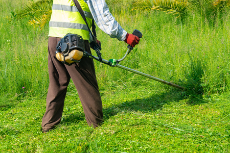 The gardener cutting grass by lawn mower, lawn care. Nature Imagens