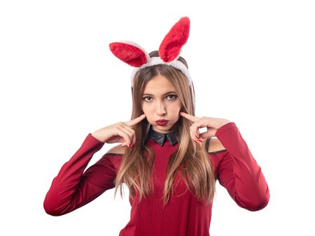 Beautiful girl with rabbit accessory posing on white background. Celebration.