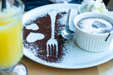 Chocolate Souffle with ice cream. Fork and hearts silhouettes next to it. Dessert.