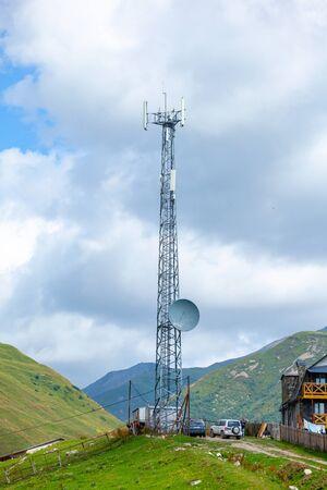 Telefonantenne, blauer Himmel und weiße Wolken in Ushguli, Swanetien, Georgien. Telekommunikation.