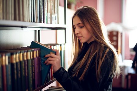 Beautiful teenager schoolgirl reading a book in the library, education.