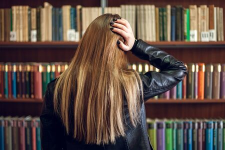 Beautiful teenager schoolgirl standing in the library and choosing a book, education