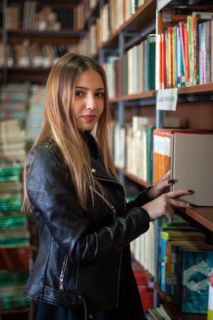 Beautiful teenager schoolgirl choosing a book in the library, education
