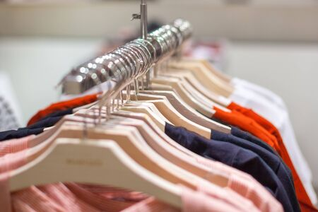 Clothes hang on a shelf. Clothes hanger showcase in store shopping. Shop Banco de Imagens