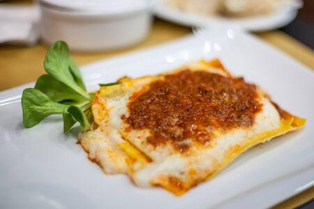 Lasagna served on a white plate with salad. Italian tradicional food.