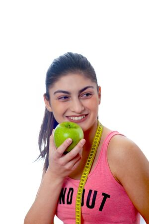 Beautiful young healthy girl with apple and measure. Diet. Isolated on white background. Sport. Фото со стока