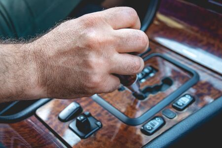 Driver man hand holding automatic transmission in car. Male hand changing levels of automatic gearbox in the car. Transportation. Reklamní fotografie