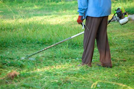 The gardener cutting grass by lawn mower, lawn care. Nature.