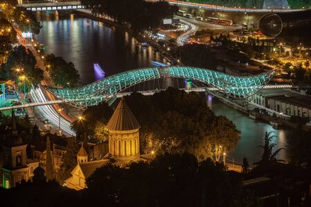 Overview at the futuristic bridge made of glass and metal over a Mtkvari river. Travel. Reklamní fotografie