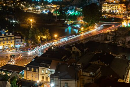 Car lights along Metekhi bridge in Tbilisi, Georgia, at night. Europe square, left bank of Kura river. Travel.