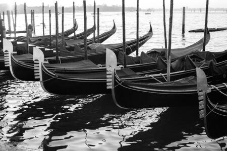 Gondolas by Saint Mark square at sunrise, Venice, Italy. Travel. B&W