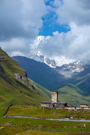 View of the Ushguli village at the foot of Mt. Shkhara. Lamaria Monastery, old Rock tower. Travel.