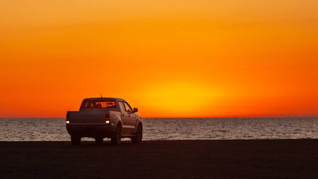 Pick-up truck parked in front of Black Sea at beautiful sunset. Nature.