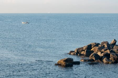 Fisherman in a boat fishing in the early morning. Mediterranean Sea. Italy. Stock fotó