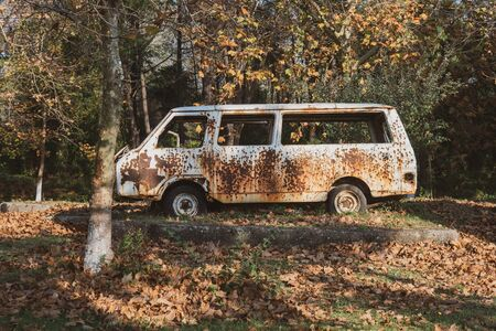 Old abandoned rusty car in a park. Vintage. Banco de Imagens