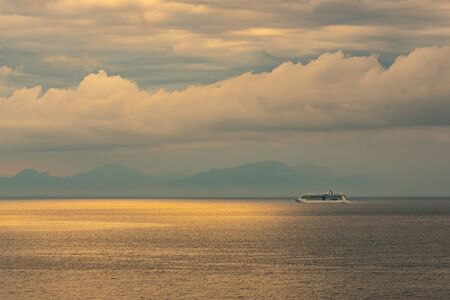 Distant view of touristic ship in the mediterranean sea. Cloudy day. Travel. Italy.