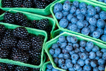 Fresh blueberries and blackberries at the market. Fruits.