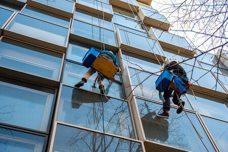 Arbeiter wäscht Fenster eines Gebäudes, das an Seilen hängt. Gebäude. Standard-Bild