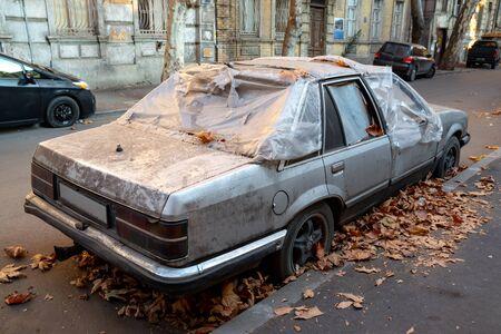 Rusty abandoned car on a city street. Tbilisi, Georgia