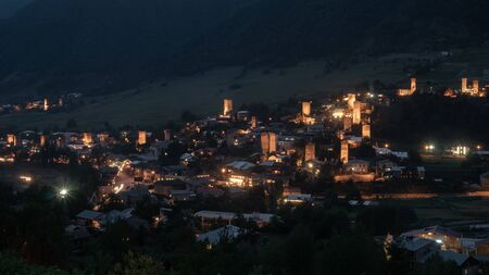Night view on Mestia with its beautiful illuminated Svan Towers and high mountains. Svaneti, Georgia. Travel.
