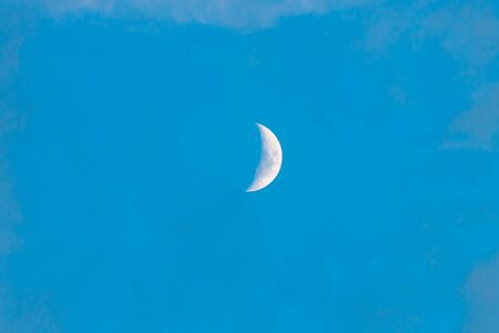 young moon on light blue sky, quarter moon. Space.