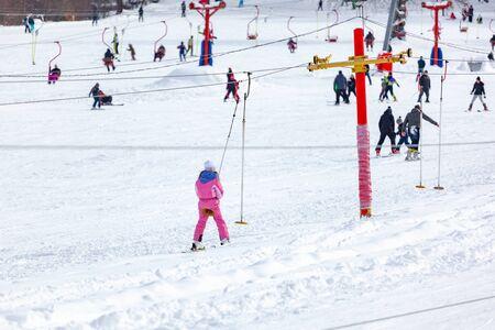 Skiers skiing climb a yoke on a mountain. Light skiing track in Bakuriani. Winter resort.